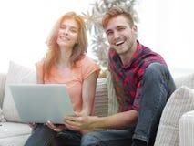 Couples de sourire se reposant à la maison, se reposant sur le divan Images libres de droits