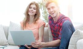 Couples de sourire se reposant à la maison, se reposant sur le divan Image libre de droits