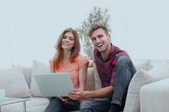 Couples de sourire se reposant à la maison, se reposant sur le divan Photos stock