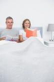 Couples de sourire se reposant dans des livres de lecture de lit Image libre de droits