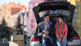 Couples de sourire se reposant dans le tronc de la voiture moderne banque de vidéos