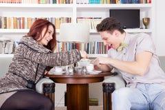 Couples de sourire se reposant dans les chaises dans le salon photographie stock