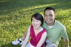 Couples de sourire se reposant sur l'herbe - horizontale images stock