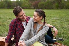 Couples de sourire se reposant sur la couverture en parc Image stock