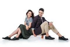 Couples de sourire se reposant sur la planche à roulettes d'isolement sur le blanc Photos libres de droits