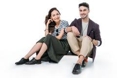 Couples de sourire se reposant sur la planche à roulettes et regarder l'appareil-photo Photographie stock libre de droits