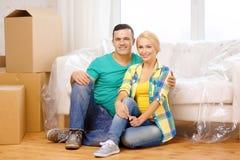 Couples de sourire se reposant sur le plancher dans la nouvelle maison photos libres de droits