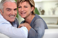 Couples de sourire se reposant sur un sofa Photo stock