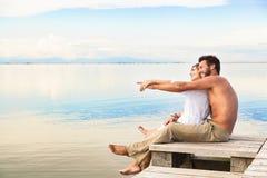 Couples de sourire se reposant sur une jetée et indiquant l'horizon Photo libre de droits