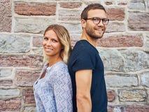 Couples de sourire se tenant de nouveau au dos contre le mur Photos stock