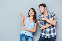 Couples de sourire se tenant et se dirigeant à quelque chose au-dessus du fond gris Photo stock