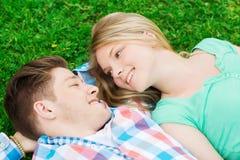 Couples de sourire se trouvant sur l'herbe en parc Photos libres de droits