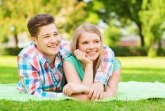 Couples de sourire se trouvant sur la couverture en parc Photos stock