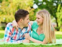 Couples de sourire se trouvant sur la couverture en parc Photo libre de droits