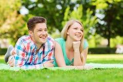 Couples de sourire se trouvant sur la couverture en parc Photographie stock