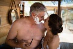 Couples de sourire semblant face à face tout en rasant en cottage Photo stock