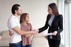 Couples de sourire serrant la main à l'agent immobilier sur se réunir d'intérieur Image libre de droits