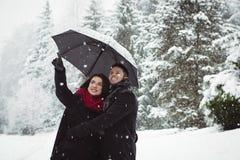 Couples de sourire sous le parapluie se dirigeant à la vue dans la forêt Photographie stock