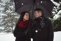 Couples de sourire sous le parapluie se tenant dans la forêt Images libres de droits