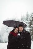 Couples de sourire sous le parapluie utilisant le téléphone portable dans la forêt Photos stock