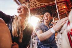 Couples de sourire sur le carrousel au champ de foire Photos libres de droits