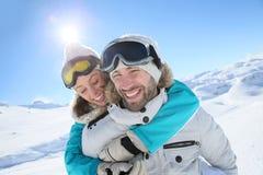 Couples de sourire sur les pentes de ski Photos stock
