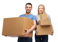 Couples de sourire tenant des boîtes en carton Photo stock
