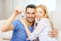 Couples de sourire tenant des clés à la maison Image stock