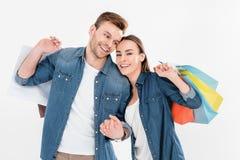 Couples de sourire tenant des paniers sur le blanc, femme regardant à l'appareil-photo image libre de droits