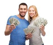 Couples de sourire tenant l'argent d'argent liquide du dollar Photos stock