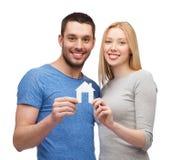 Couples de sourire tenant la maison de livre blanc Photographie stock
