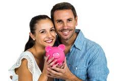 Couples de sourire tenant la tirelire rose Photographie stock