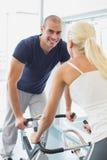 Couples de sourire travaillant aux vélos d'exercice au gymnase photo stock