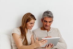 Couples de sourire utilisant l'ipad Photo stock