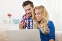 Couples de sourire utilisant l'ordinateur portable Photo stock