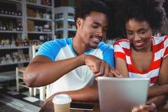 Couples de sourire utilisant le comprimé numérique en café Photo libre de droits