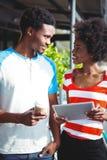 Couples de sourire utilisant le comprimé numérique en café Image stock