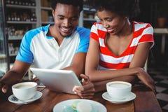 Couples de sourire utilisant le comprimé numérique en café Images libres de droits