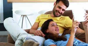 Couples de sourire utilisant le comprimé numérique sur le sofa dans le salon banque de vidéos