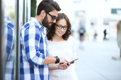 Couples de sourire utilisant le téléphone intelligent ensemble dans la ville photographie stock libre de droits