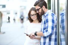Couples de sourire utilisant le téléphone intelligent ensemble dans la ville Image libre de droits