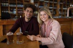 Couples de sourire utilisant le téléphone portable tout en ayant le verre de bière dans la barre Photo libre de droits