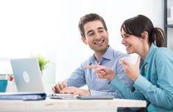 Couples de sourire utilisant un ordinateur portable Photo stock