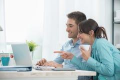 Couples de sourire utilisant un ordinateur portable Photographie stock