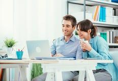 Couples de sourire utilisant un ordinateur portable Images stock