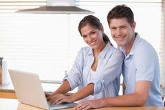 Couples de sourire utilisant un ordinateur portatif Image libre de droits