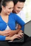 Couples de sourire utilisant un ordinateur portatif Photographie stock libre de droits