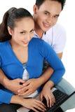Couples de sourire utilisant un ordinateur portatif Images libres de droits