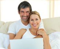 Couples de sourire utilisant un ordinateur portatif se situant dans le bâti Photographie stock libre de droits