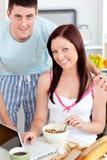 Couples de sourire utilisant un ordinateur portatif tandis que déjeuner Image libre de droits